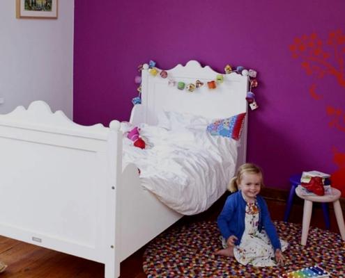 meisje zit naast bed te spelen